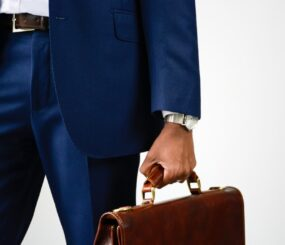 close-up-of-stylish-young-businessman-in-blue-formal-wear-holding-briefcase-man-in-business-suit_t20_VLjkNb