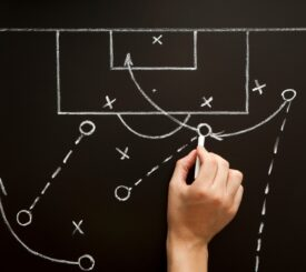 soccer-football-coach-explaining-the-game-tactics-on-blackboard-in-the-locker-room_t20_a7G6Rw